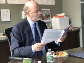 Gov. Wolf looks over a report on progress